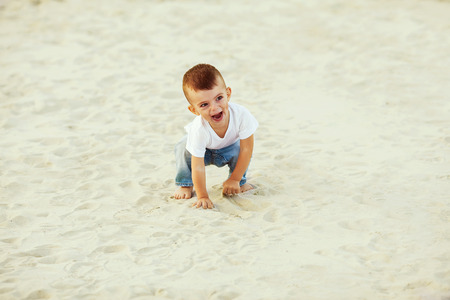 boy laughing in the sand, walking along the beach photo