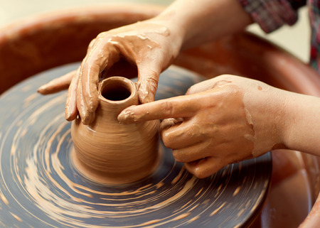Hands working on pottery wheel photo