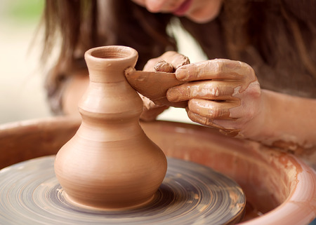 handicrafts: Hands working on pottery wheel
