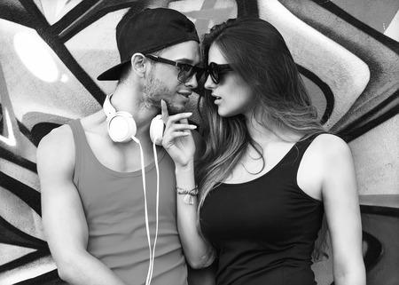 fashion couple with sunglasses  near the wall graffiti photo
