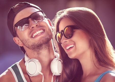 Close up portrait of happy smiling hipster couple in love. Wearing retro clothes and sunglasses. Fashion. Vogue. Listen to music and laugh. photo