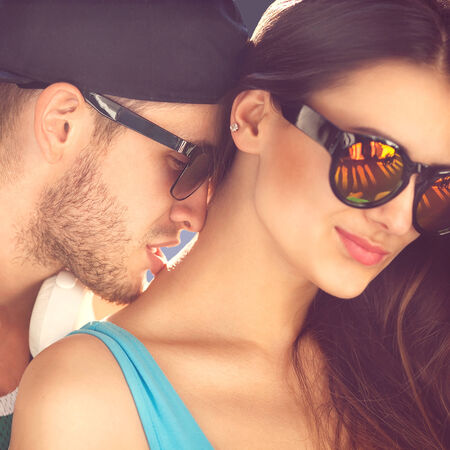 Close up portrait of happy smiling hipster couple in love. Wearing retro clothes and sunglasses. He kisses her on the neck, fashion. Vogue photo