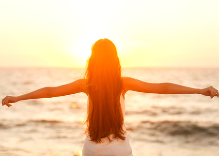 sun worship: Free woman enjoying freedom feeling happy at beach at sunset. Beautiful serene relaxing woman in pure happiness and elated enjoyment with arms raised outstretched up.  Stock Photo