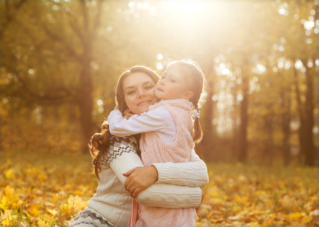 kid portrait: Mother and daughter having fun in the autumn park among the falling leaves.