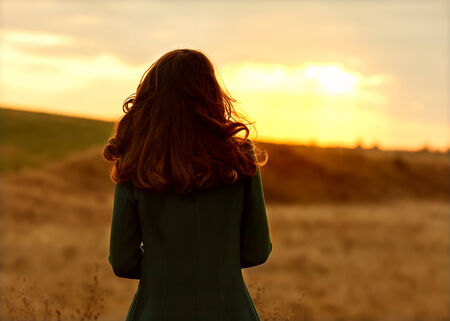 girl in autumn at sunset standing in a field. Silhouette. photo