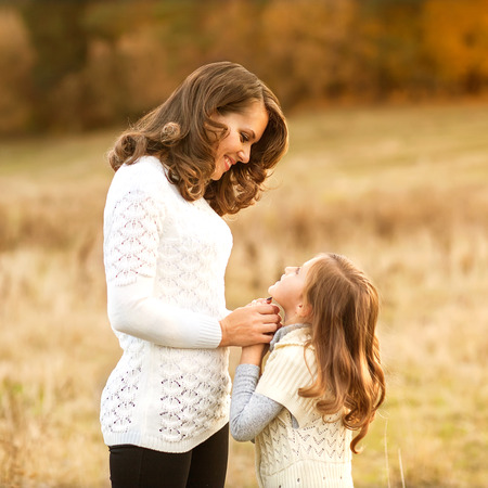 mother and daughter walking in autumn in a field photo