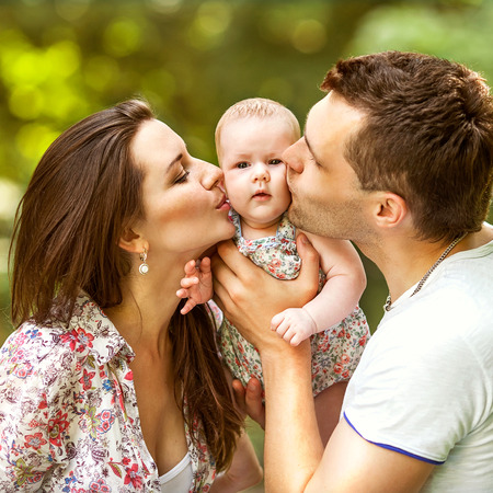 happy mother and father kissing his little daughter  in park Stock Photo