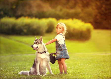 person outdoors: little girl in the park their home with a dog Husky