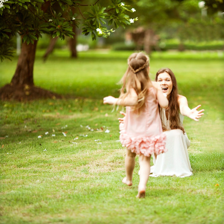 adult child: mother and daughter walking in the park, happy at sunset in Bangkok, Thailand.