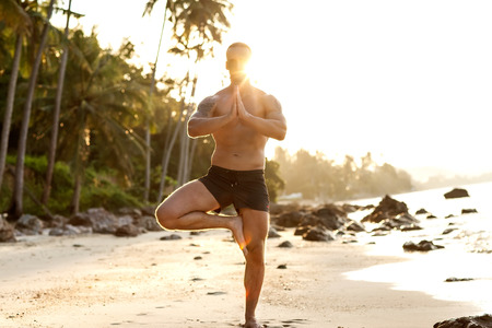 man practice yoga on the beach at sunset photo