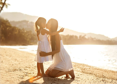 mother and daughter happy in love at sunset