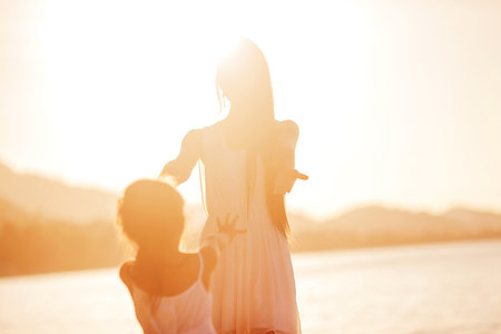 happiness people silhouette on the sunset: mother and daughter happy in love at sunset Stock Photo