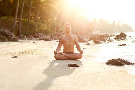 man practice yoga on the beach at sunset photo