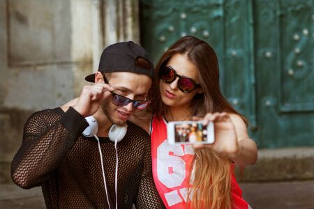 Sommer: Young fashion couple taking selfie in the city