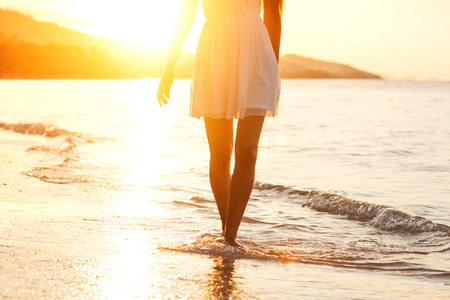 white beach: Beautiful girl walking on the beach at sunset, freedom concept Stock Photo