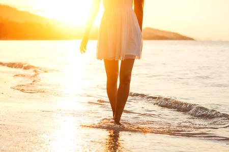 Mooi meisje lopen op het strand bij zonsondergang, vrijheid concept