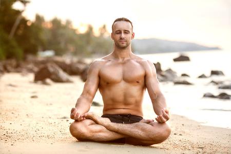 hombre la práctica de yoga en la playa al atardecer