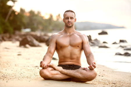 man practice yoga on the beach at sunset