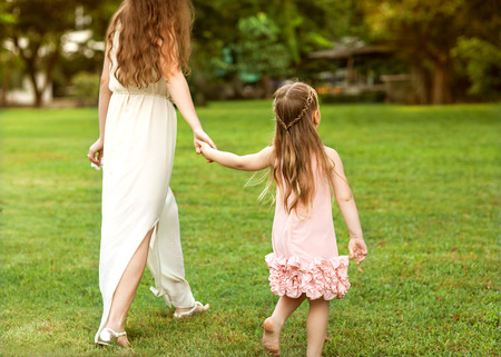 mother and daughter walking in the park holding hands in love photo