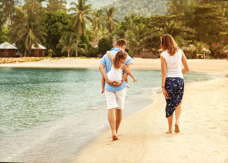 happy family walking on the sea on the beach photo