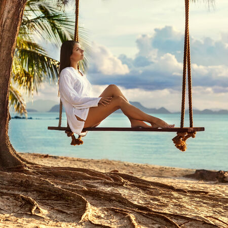 girl sitting on the swing near the palm trees on the beach photo