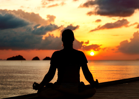 man doing yoga at sunset