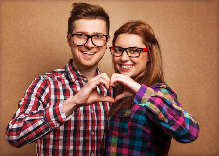 Young couple in love make a heart gesture Фото со стока