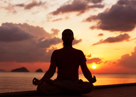 man doing yoga at sunset photo
