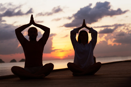man and woman practicing yoga at sunset photo