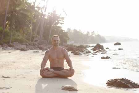 salutation: Fit young man practices sun salutation yoga on the beach at sunset Stock Photo
