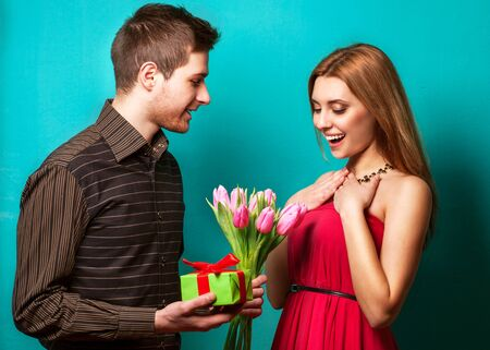 adult valentine: Portrait of young couple in in love posing at studio dressed in classic clothes. the guy gives her flowers and a gift, concept of Valentines Day