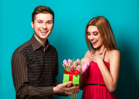 Portrait of young couple in in love posing at studio dressed in classic clothes. the guy gives her flowers and a gift, concept of Valentines Day photo