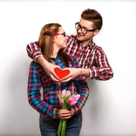 Young couple in love make a heart and hands are holding a bouquet of tulips. The concept of Valentines Day Stock Photo: photo