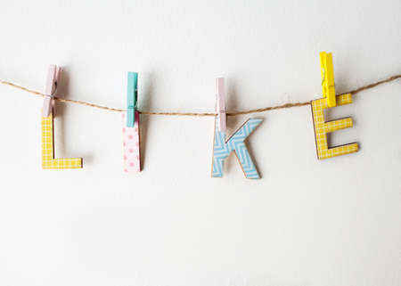wall hanging: Like word on a white wall hanging on colored clothespins Stock Photo