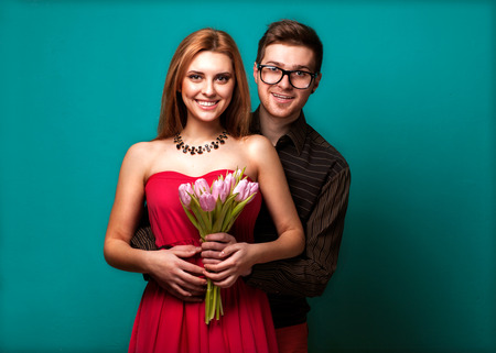 Portrait of young couple in in love posing at studio dressed in classic clothes. the guy gives her flowers and a gift, concept of Valentines Day