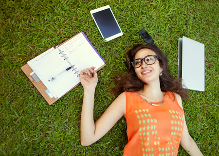 freelancer girl from the device: laptop, tablet, player, notebook, lying on the grass and working