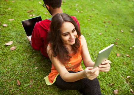 girl and her boyfriend sitting on the grass and working in the tablet and laptop photo