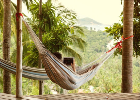 e reading: man lying in a hammock freelancer and running, beautiful mountain views, drinking wine Stock Photo