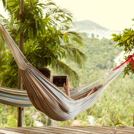 e book: man lying in a hammock freelancer and running, beautiful mountain views, drinking wine Stock Photo