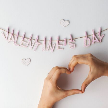fun day: Valentines Day Heart from hands on a white background hanging words