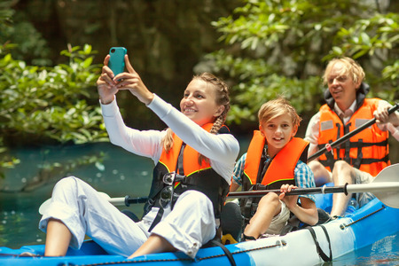 family kayaking and makes selfie photo