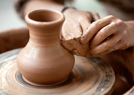 Hands working on pottery wheel