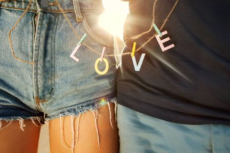 holding hands: Young couple in love walking in the park holding hands looking in the sunset, words love Stock Photo
