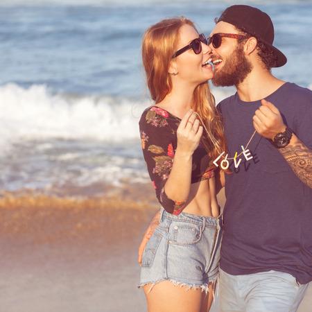 baiser amoureux: Jeune couple amoureux marche dans les mains de mer tenant regardant dans le coucher du soleil, concept de Saint Valentin Banque d'images