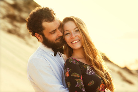 happy young couple: happy couple in love on the sand dunes, concept of Valentines Day Stock Photo