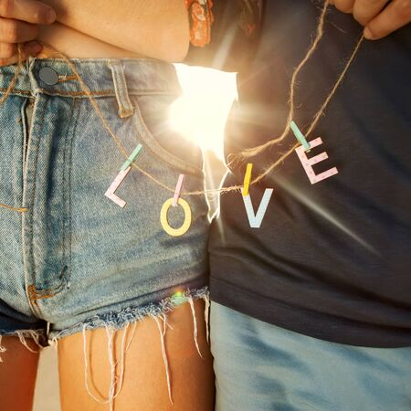 love park: Young couple in love walking in the park holding hands looking in the sunset, words love Stock Photo