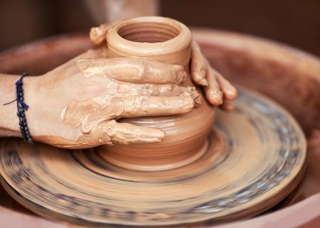 Handen werken op pottenbakkersschijf