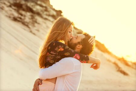 xwhite: Young couple in love walking in the sea holding hands looking in the sunset, concept of Valentines Day Stock Photo