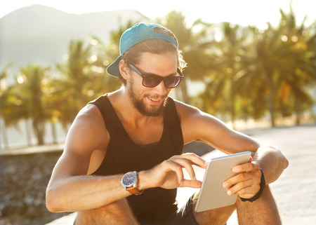 fashion guy sitting on the tablet, running in sunglasses on the beach with views of the mountains Foto de archivo