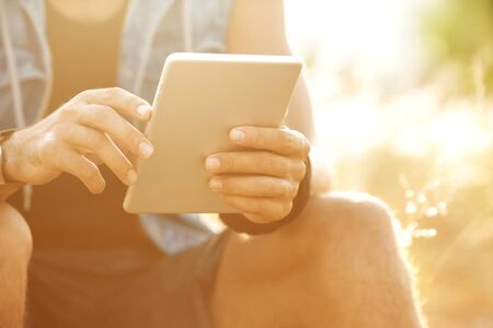 tablet: sunny tablet in the hands of the guy on the nature Stock Photo